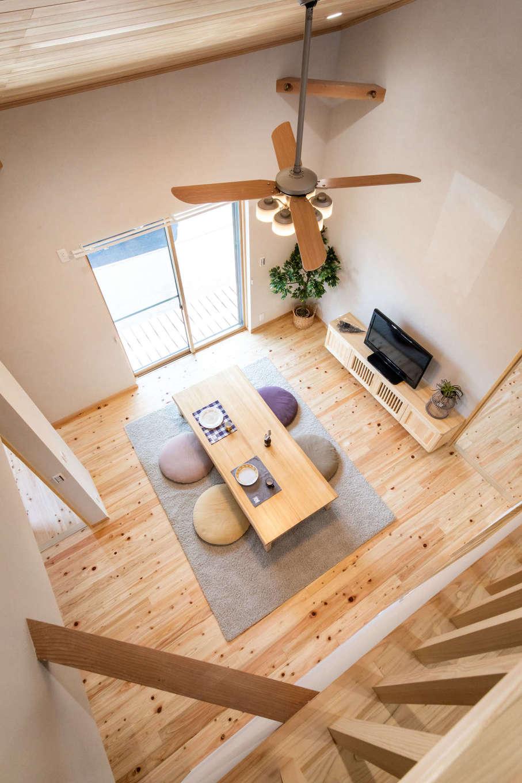 今井建設【デザイン住宅、間取り、自然素材】いちばんの見どころは、開放感あふれる吹抜けのリビング。勾配天井なので、より広く感じられる。大きな吹抜けを通して、キッチンにいても2階の気配がわかるので安心。床は無垢のヒノキ、天井はパイン材で、経年変化も楽しみ