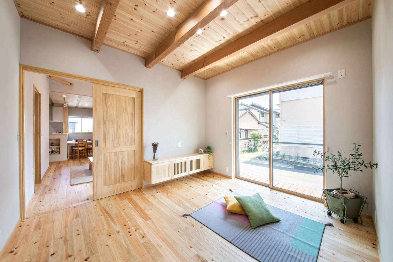 今井建設【デザイン住宅、間取り、自然素材】7畳の主寝室。この部屋だけ梁を現しにして変化をつけた。3畳のウォークインクローゼットにはアイロンがけもできる家事コーナーを造作