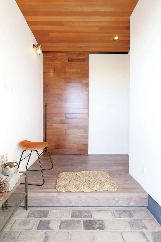 丸昇彦坂建設【デザイン住宅、趣味、インテリア】玄関、リビングドアの天壁に異なる種類の部材を採用しながらも一体感を出した。三和土はアンティークレンガ。マリンランプも映える独創的な空間