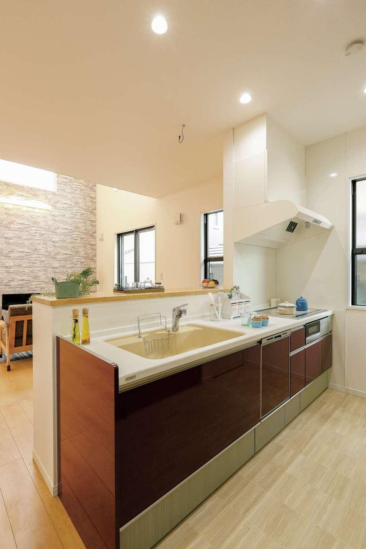 丸昇彦坂建設【収納力、省エネ、インテリア】家族の様子を見渡しながら調理できる対面キッチン。ダークカラーのパネルが白を基調とした空間の差し色になっている