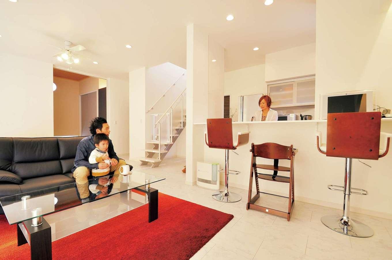 丸昇彦坂建設【デザイン住宅、子育て、インテリア】モダンなリビングは白を基調としたLDKに赤いラグマットが差し色に。キッチンからは和室まで見渡せるので子育てママも安心。床は高級感のある大理石調の鏡面フローリングを使用