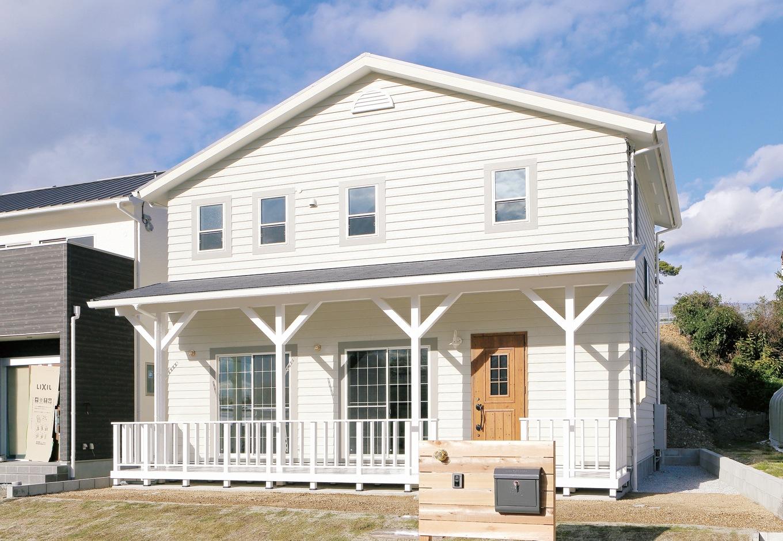 丸昇彦坂建設【デザイン住宅、輸入住宅、趣味】カヴァードポーチが美しいアーリーアメリカンの外観。外壁はラップサイディングを採用し、ハワイの邸宅のニュアンスを出した。木の扉がアクセントに