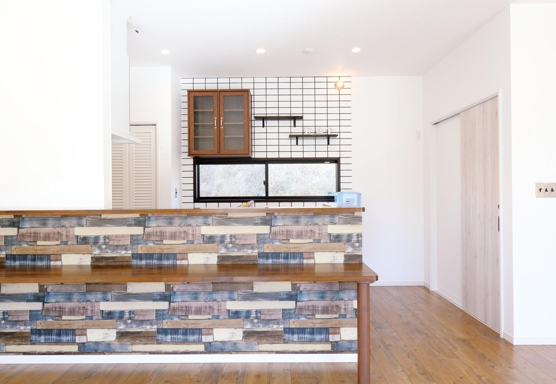 丸昇彦坂建設【デザイン住宅、輸入住宅、趣味】ドイツ製の独創的なデザインのクロスを張ったキッチン。バックヤードのタイル、食器棚はSさんの持ち込み