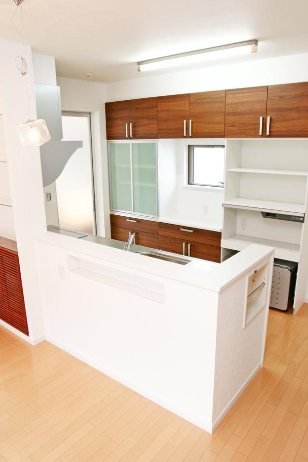 丸昇彦坂建設【デザイン住宅、収納力、和風】奥さまお気に入りの対面式キッチンに立つと、和室やリビングで過ごす家族の息づかいがよくわかる。カウンター部分にある調味料入れや、新聞収納用のニッチも便利