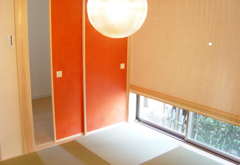 丸昇彦坂建設【デザイン住宅、収納力、和風】小上がりの畳スペースが広がる和室も、小窓を設けて庭を感じる造りに。温かみある照明の光がよく映える。オレンジ色の襖の向こうには、収納力抜群の納戸を用意