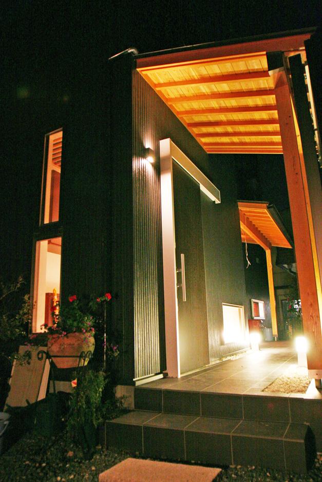丸昇彦坂建設【デザイン住宅、収納力、和風】無垢材の天井を持つ庇や、白い玉砂利が和を感じさせる玄関アプローチ。照明の使い方もシック