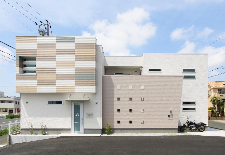 丸昇彦坂建設【デザイン住宅、間取り、インテリア】ユニークな色使いが目を引く外観。生活感を隠すために、家族用の玄関や2階ベランダは飾り壁で覆っている