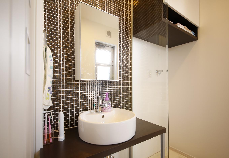 丸昇彦坂建設【デザイン住宅、間取り、インテリア】洗面スペースもモダンなデザインに仕上げた。モザイクタイルを張り付けた壁が印象的だ