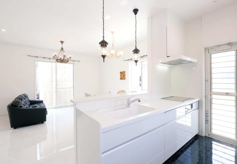 丸昇彦坂建設【デザイン住宅、輸入住宅、インテリア】白で統一したキッチン。鏡面仕上げの黒い床に空が映り込んで、まるで宙に浮いているみたい