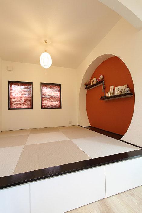 丸昇彦坂建設【輸入住宅、趣味、ガレージ】丸い飾り棚と、オレンジ色のアクセントウォールが目を引く小上がりの畳コーナー。個性的で可愛らしい雰囲気がリビングとしっくりなじんでいる。床下には引き出し収納があり、子どものおもちゃなどをすっきりしまえて便利