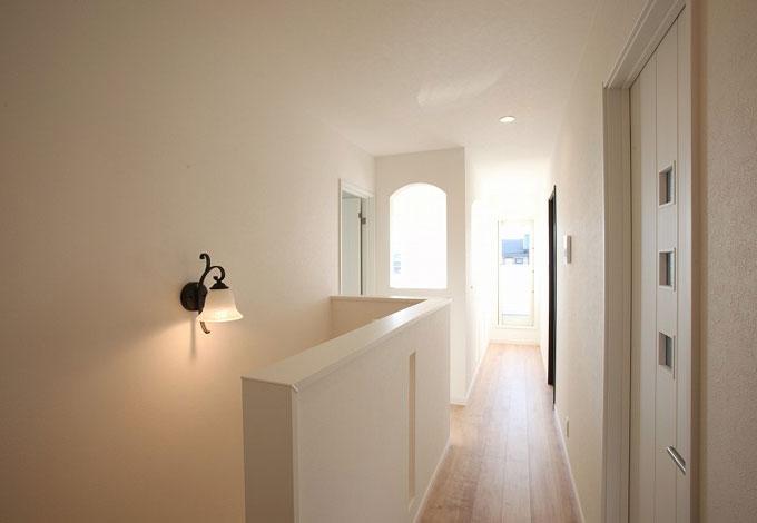 丸昇彦坂建設【輸入住宅、趣味、ガレージ】白で統一した清楚な雰囲気の階段ホール。アーチ型の壁から顔をのぞかせて、階下の家族に声を掛けることもできる。廊下の正面奥にはバルコニーがある