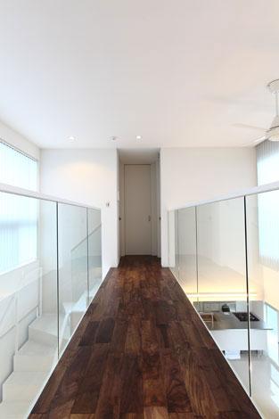 丸昇彦坂建設【デザイン住宅、間取り、ガレージ】吹抜けに橋を架けたかのような2階の廊下は、プライベートルームと洗面・浴室スペースをつないでいる。両側の手すり部分にスケルトンガラスを用い、明るさと開放感を確保した