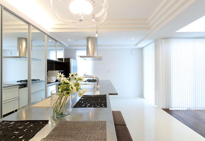 丸昇彦坂建設【デザイン住宅、間取り、ガレージ】キッチンと一列に配置したステンレスのダイニングテーブル。調理や盛り付けのスペースを広く確保でき、配膳や片づけも便利