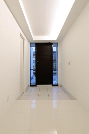 丸昇彦坂建設【デザイン住宅、間取り、ガレージ】天井の間接照明が優雅な雰囲気を演出する玄関。左側の扉の先は土間収納とガレージに通じている