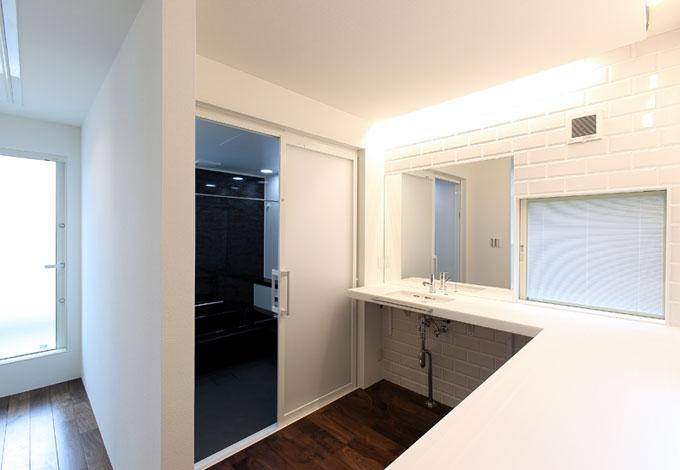 丸昇彦坂建設【デザイン住宅、間取り、ガレージ】2階の洗面コーナーはカウンターをL字型に配置してあるので、アイロンがけや洗濯物をたたむのにも便利。左手奥がバルコニーになっていて動線も考慮
