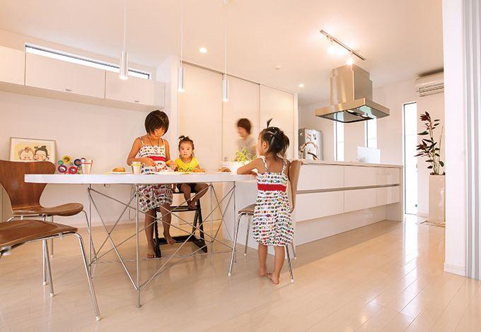 丸昇彦坂建設【デザイン住宅、子育て、間取り】アイランドキッチンと変形テーブルを一列に配置し、調理や片付けがラクにできるダイニングキッチン
