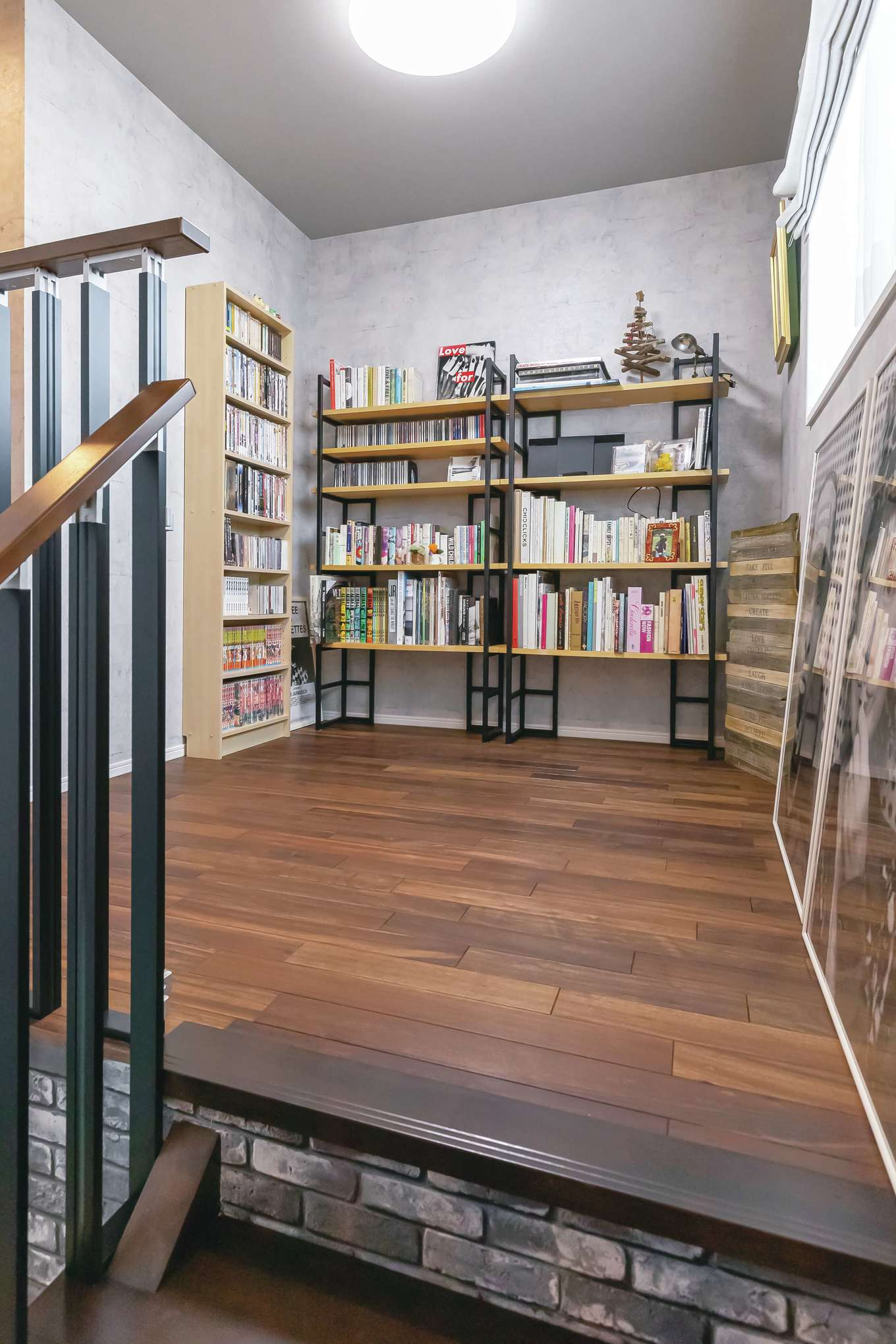 丸昇彦坂建設【1000万円台、デザイン住宅、子育て】階段を上がった先にあるフリースペース。壁に本棚を造作し、夫婦の愛読書や雑誌、写真集、コミック、DVDなどがずらりと並ぶ。