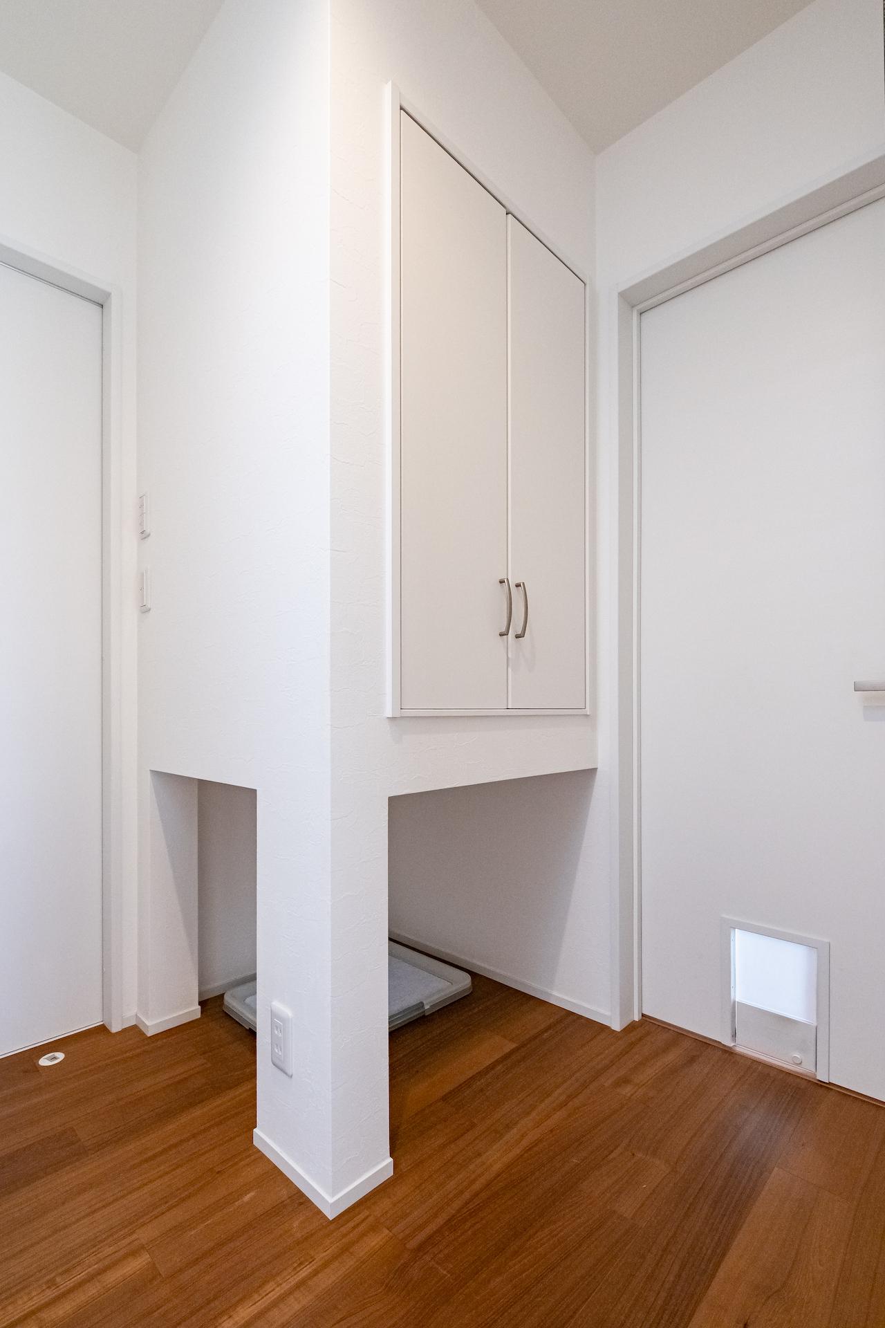 金子工務店/めぐみ不動産(アイフルホーム 沼津店)【デザイン住宅、間取り、ペット】廊下の一角に設けられたワンちゃんのトイレスペース。上部の収納にはえさやグッズが収納できる。写真右下のドアはLDKへの通り道