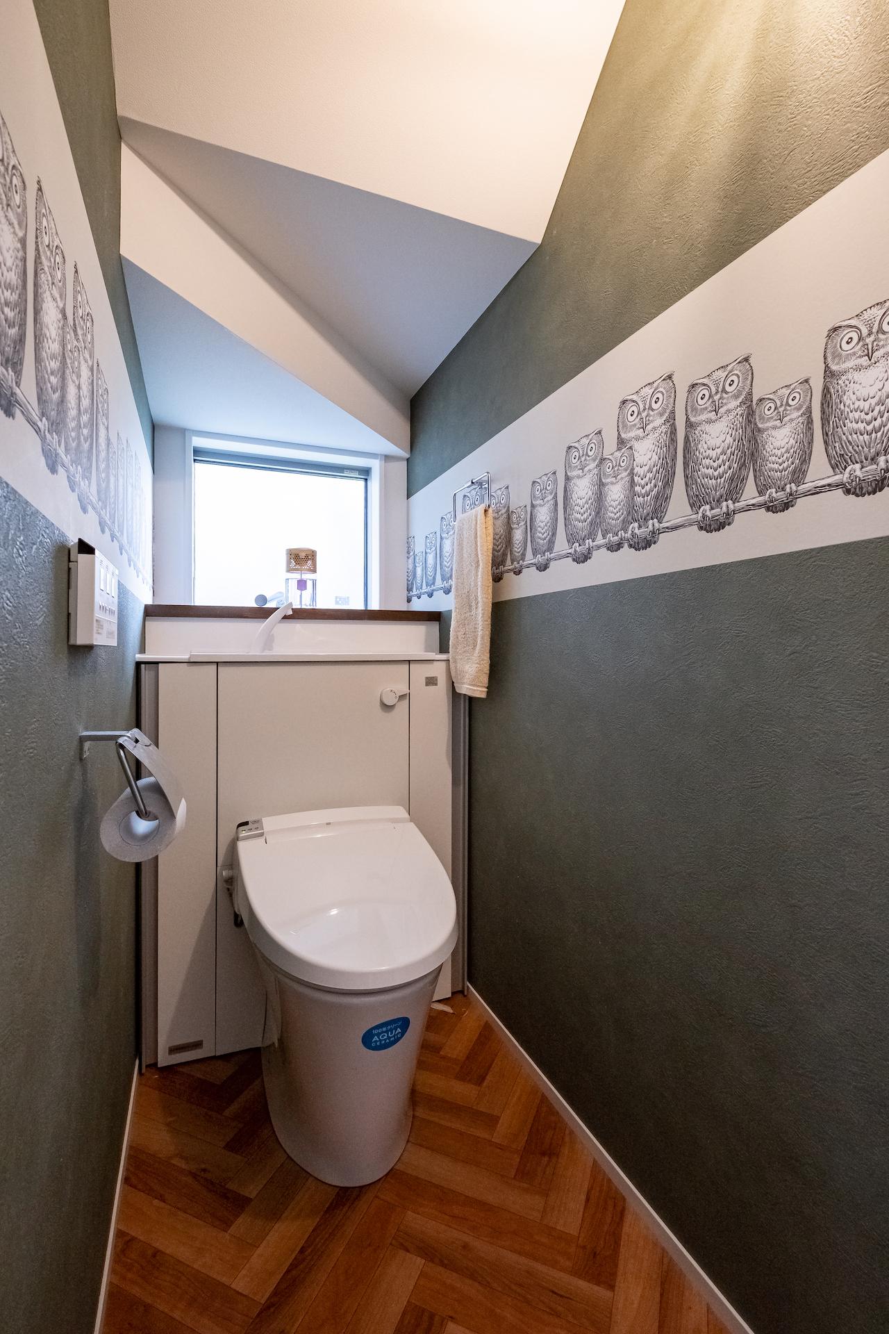 ふくろう柄の輸入クロスがかわいいトイレは階段下スペースを活用。タンク部分を収納に隠し、スッキリさせた