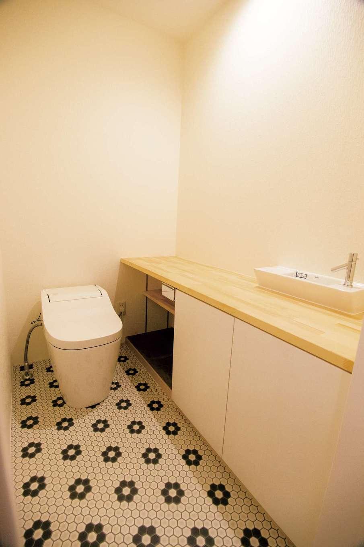 収納カウンターを大きめに取ったトイレ。花柄タイルモチーフのフロアがレトロな雰囲気でかわいい