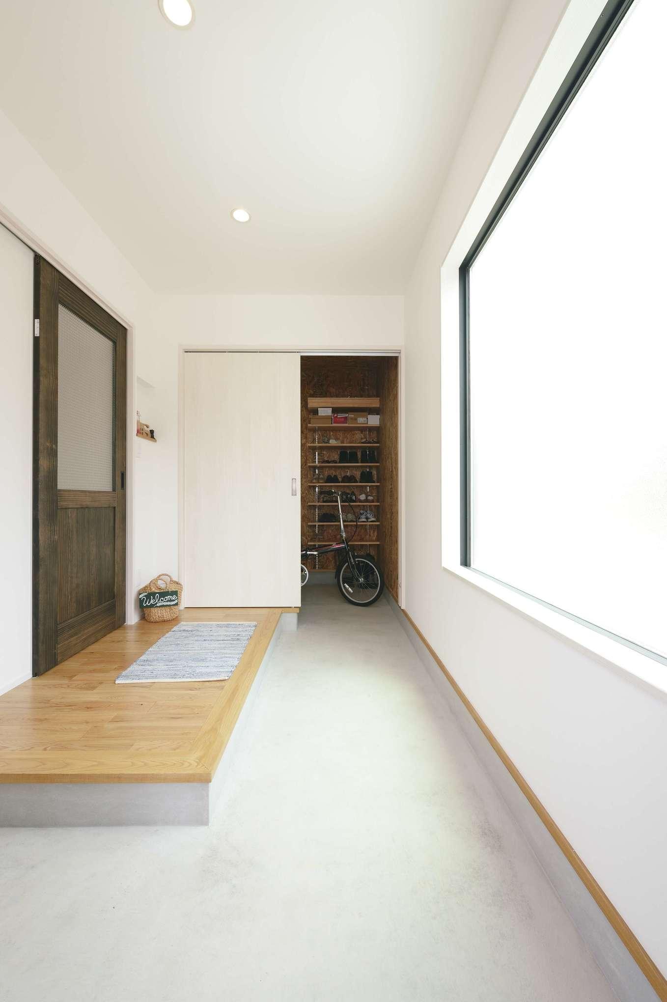 小玉建設【デザイン住宅、自然素材、間取り】奥に延びる広い土間のある玄関。壁には大きなフィックス窓を取り付け、充分な明るさを確保している。使いやすい土間収納も完備