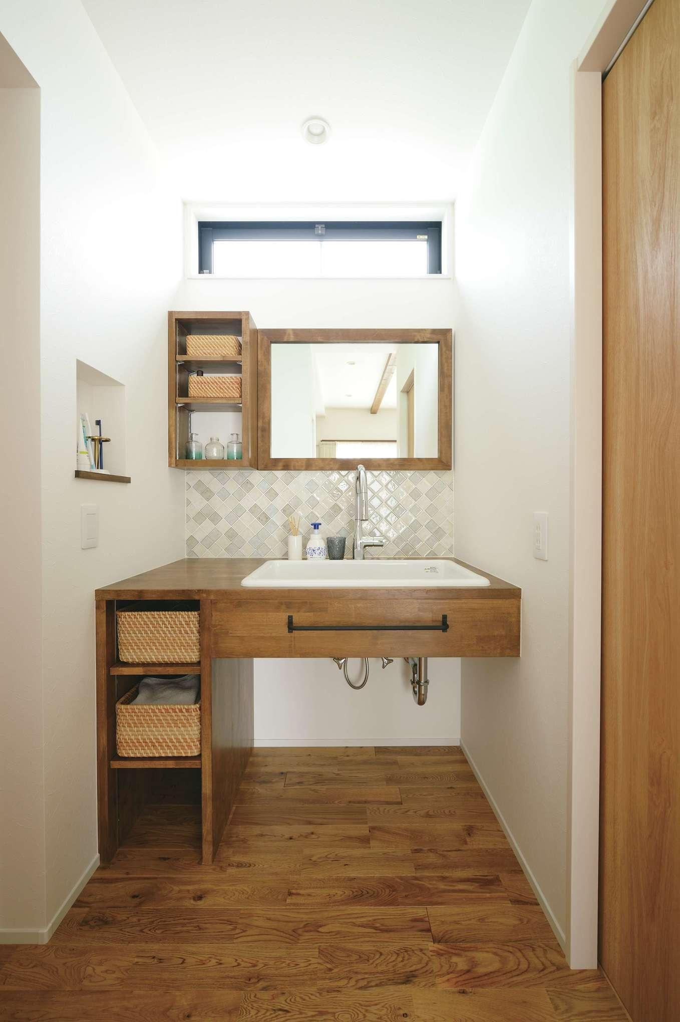 小玉建設【デザイン住宅、自然素材、間取り】ダークな木材とタイル使いで、シンプルな空間に仕上げた造作洗面台。棚とニッチが使いやすい