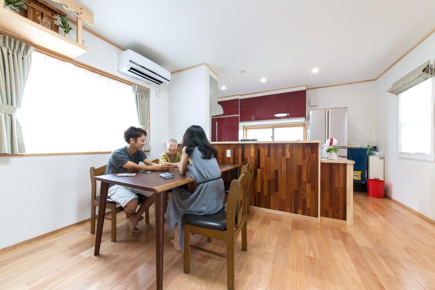 小玉建設【デザイン住宅、二世帯住宅、自然素材】1階のダイニングスペース。カウンターキッチンの壁は、カリンの木を使用。濃いブラウンがアクセントとして効いている