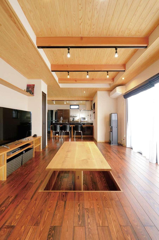 タツミハウジング【自然素材、省エネ、間取り】茶色に着色したスギの床が落ち着きを感じさせるLDK。壁は珪藻土塗り、天井はスギ板張りにして、体にやさしい自然素材の空間を実現。リビングに設けた掘りごたつ式テーブルは、夫妻が同社の「木のモデルハウス」を見てとり入れたもの