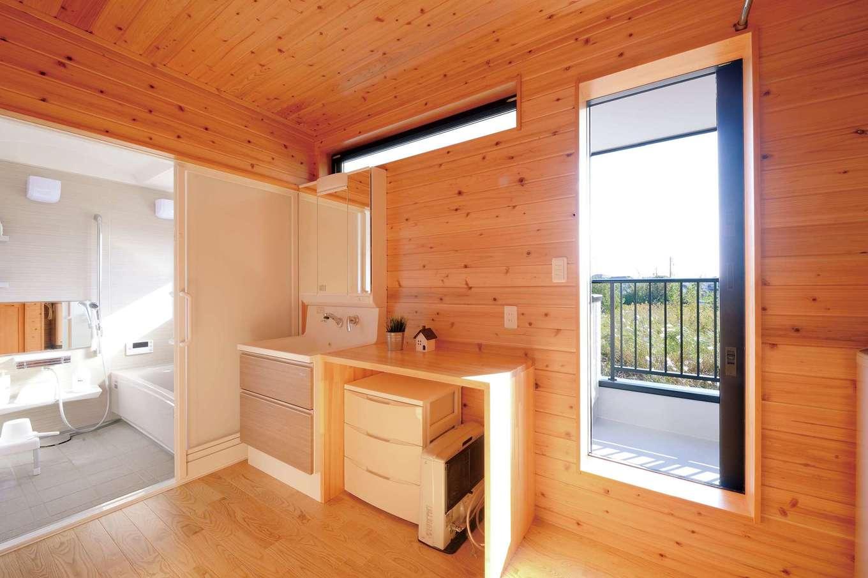タツミハウジング【自然素材、省エネ、間取り】隣地で園芸農業を営むご主人が使う土間収納や書斎を確保するため、洗面・浴室は2階に配置。「おかげで洗濯物をベランダに干すのもラクで助かっています」と奥さま。壁・床・天井が丸ごと木の空間とベランダから注ぐ陽光が清々しい