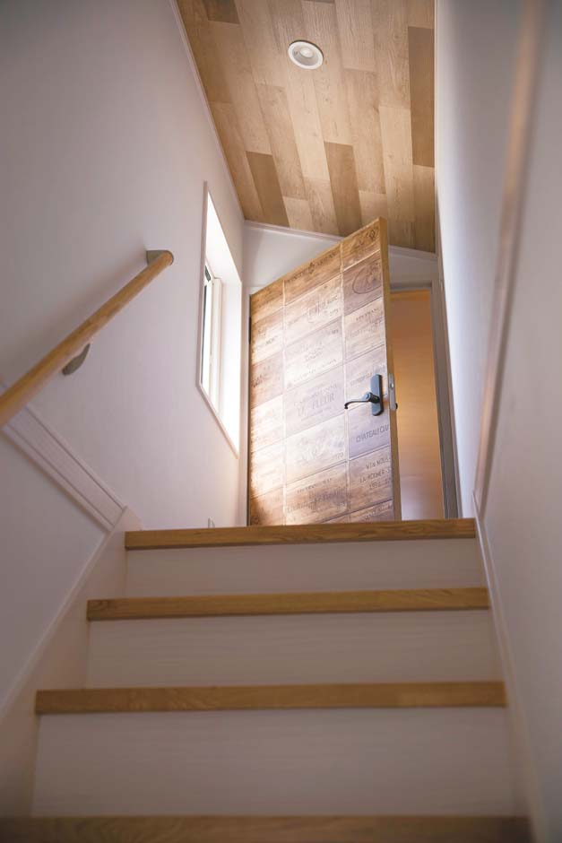 タツミハウジング【デザイン住宅、間取り、インテリア】階段上の小屋裏には、山小屋風のご主人のこもり部屋がある。ブルックリンテイストのクロスを張ったドアはご主人のこだわり