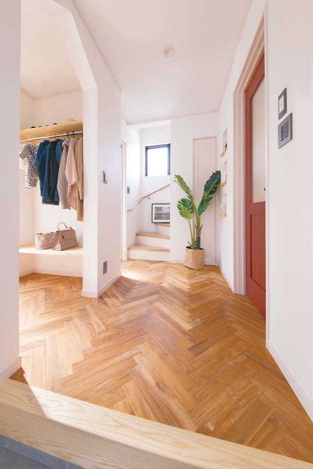 タツミハウジング【デザイン住宅、間取り、インテリア】「CHU!の家」モデルハウスの玄関を真似て、床の無垢板をヘリンボーン柄に。赤い室内ドアともベストマッチ