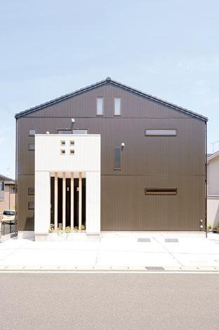 タツミハウジング【1000万円台、子育て、自然素材】こげ茶色のシンプルなフォルムに白い玄関ポーチが映える外観。地震の揺れを2分の1にする超制震住宅の構造を採用している