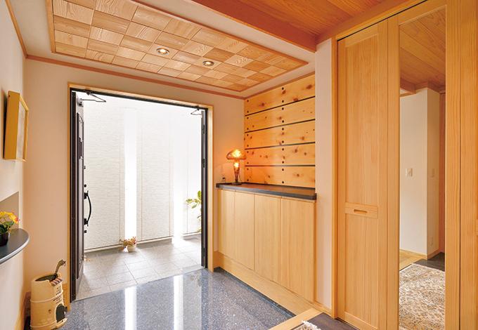 タツミハウジング【収納力、自然素材、屋上バルコニー】玄関は御影石。天井や壁に細工が施され、上質感が漂う。玄関収納も大容量