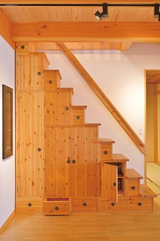 タツミハウジング【収納力、自然素材、屋上バルコニー】建具や収納は床材や室内の雰囲気に合わせて職人さんが手づくりしている。組子技術やステンドグラスなど随所に匠の技が光る。上階へ続く箱階段は、昔の町家などに見られ、引き出しや戸棚を取り付けて階段下を有効利用したもの。モデルハウスに合わせてリメイクされた