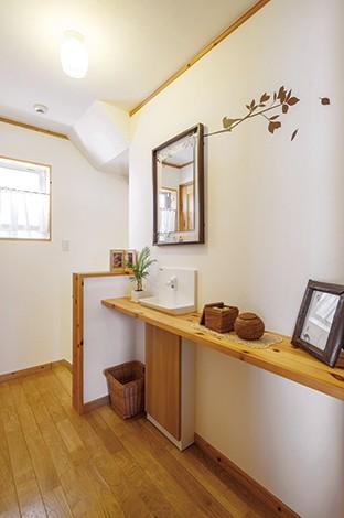 タツミハウジング【自然素材、屋上バルコニー、ガレージ】2 階廊下に設けた洗面台。カウンターと収納も造作。随所に貼ったウォールステッカーが空間のアクセントに