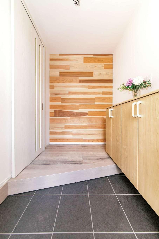 框を斜めに切ることで広く見せる玄関ホール。正面に見える無垢材のアクセントウォールは足場材を有効活用したもの