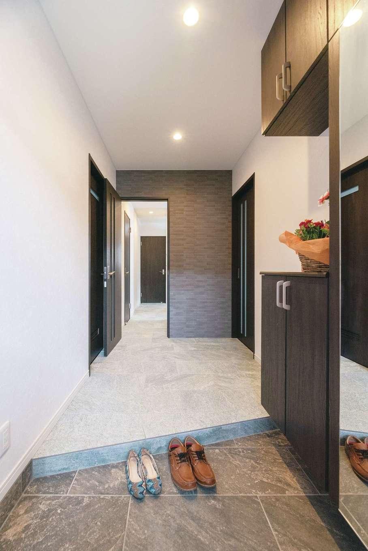 シンプル&モダンにコーディネートした子世帯の玄関ホール。框を斜めに切ったことで空間をより広く見せる。ずっと先までタイルの床が続き、奥はどうなっているのだろうとワクワクする