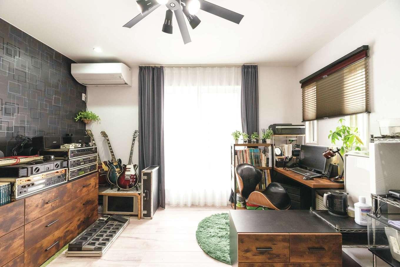 ご主人の書斎は、ミッドセンチュリーテイストのノースチェアに合わせて空間をコーディネート。マニア垂涎のギター、アンプなどが並ぶ宝箱のような空間