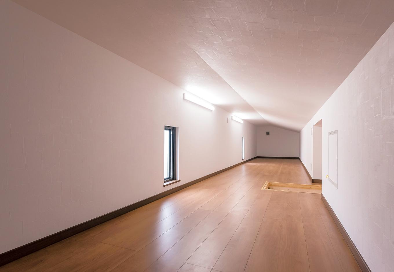 2階ホールの天井から伸びるハシゴの先には、小屋裏を利用した巨大な収納空間が小屋裏収納はおよそ12畳。当初は半分の予定だったが、せっかくだからとスペースを有効活用した結果、広い収納スペースを確保できた