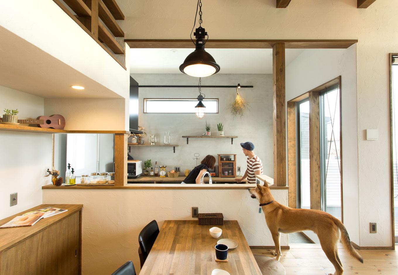 Select工房【デザイン住宅、間取り、インテリア】キッチン背面にはモルタル壁をあしらい、古材の飾り棚との相性は抜群。「猪原さんから最近『キッチンの壁には配管風の照明が合うかも』と新しいアドバイスをいただけて、参考になります」と奥さま。暮らし始めてからも、作り手と住まい手がコラボレートし続ける姿が印象的だ
