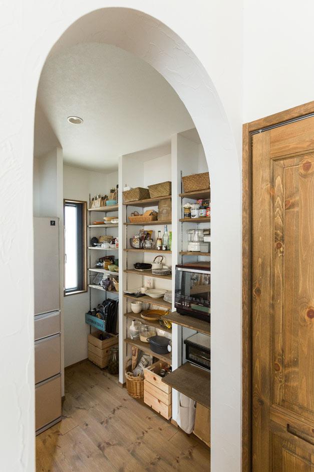 Select工房【デザイン住宅、趣味、インテリア】アーチ型の開口の奥に続くキッチンパントリー。棚板にも床と同じ塗料を塗り、ビールなど、パッケージを隠したいものは木箱に納めている。収納さえ絵になる暮らしぶりだ