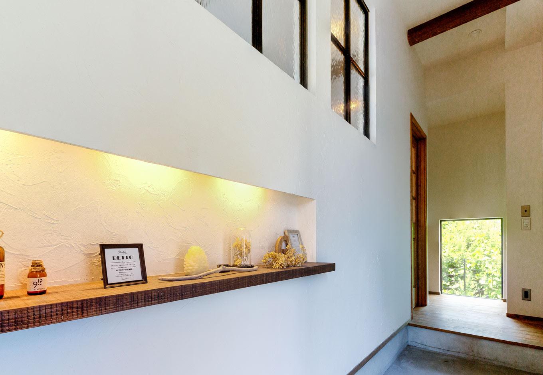 Select工房【デザイン住宅、趣味、インテリア】モルタルの土間が続く玄関には、雑貨類を並べるニッチを設計。間接照明の柔らかな光が目に心地いい。奥の窓越しに見えるグリーンも鮮やかだ