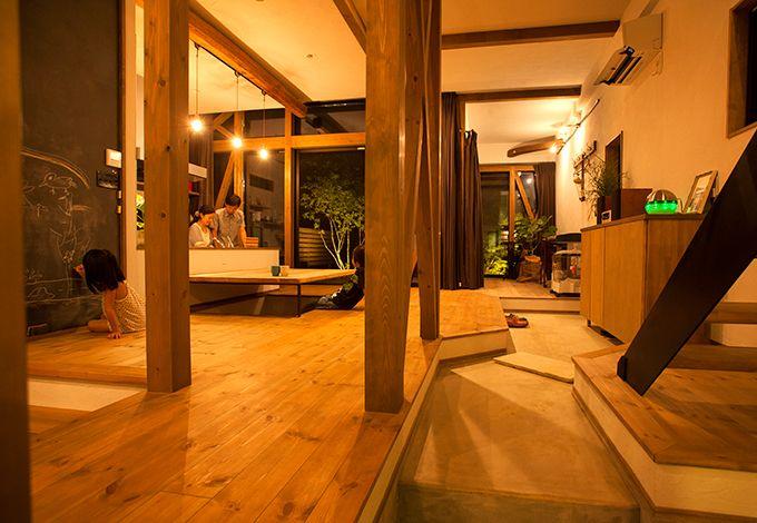 玄関からリビング、ダイニング、奥のアトリエまで続く長い土間は、どこからでもダイニングに上がれるコミュニケーションの場。奥にはライトアップされた庭の紅葉、アオダモ、シマトネリコなどの植栽が見える。リビングとダイニングの段差を設けたことで天井高が変わり、空間にリズムが生まれる。