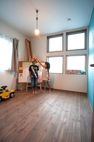 長男の部屋。ブルー系の壁は家族みんなで塗った。パイン材の床は、車のカラーデザイナーのご主人が塗料を調合して塗ったおかげで圧迫感を感じさせず、キズも目立たない
