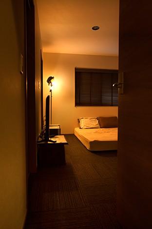 Select工房【デザイン住宅、狭小住宅、スキップフロア】主寝室は照明を暗くして落ち着いた雰囲気に。この部屋の床だけは無垢ではなく、カーペットを敷いて安らぎ感を出した。納戸を2つ備えて収納力も十分。西側の壁にどんな色を塗ろうか、ご主人は思案中