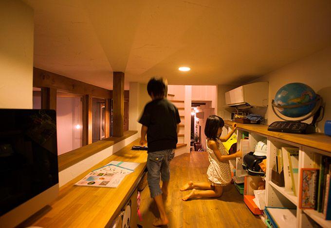 Select工房【デザイン住宅、狭小住宅、スキップフロア】スキップフロアを利用した中2階の子ども部屋。長い造作カウンターで兄妹が仲良くお勉強。ランドセルや教科書をしまえる便利な収納棚も造作。窓越しにLDKの様子が見え、キッチンから「ごはんよ〜」の声が届く