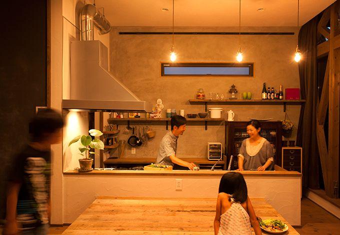 Select工房【デザイン住宅、狭小住宅、スキップフロア】料理でゲストをもてなすことが夫婦共通の趣味だけあって、こだわり抜いたダイニングキッチン。足場材で造ったダイニングは掘りごたつ式で、座るとキッチンと同じ高さの目線に。キッチンバックの棚は古材でしつらえ、アンティークな食器棚は古道具屋で購入した昔の書棚。四季折々の庭の風情を楽しみながら料理できる贅沢なキッチンだ