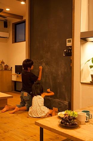 リビングとダイニングの間にある黒板。子どもが絵を描くためだけでなく、木と珪藻土のナチュラルな空間をブラックで引き締める効果も狙った