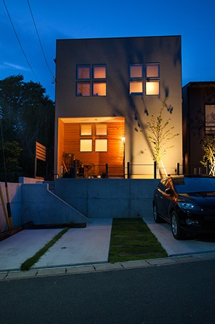 Select工房【デザイン住宅、狭小住宅、スキップフロア】シンプルですっきりとしたスクエアな外観が周囲の景観にしっくり馴染んでいる。プライバシーを確保するため、陽当たりのいい南面に大きな窓を取らず、自然の庭が広がる北面いっぱいに大開口を設けた