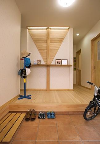隆勝工務店【子育て、収納力、自然素材】家の顔である玄関は棟梁のこだわりの1つ。正面の飾り棚には屋久杉を使用。壁に使った板は、屋根の野地板を加工したものでリビングの天井にも使われている